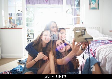 Four teenage girls taking instant camera selfie in bedroom - Stock Photo