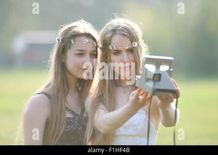 Two teenage girls in park  taking instant camera selfie - Stock Photo