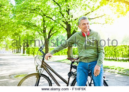 Senior man leaning against bicycle, looking away - Stock Photo