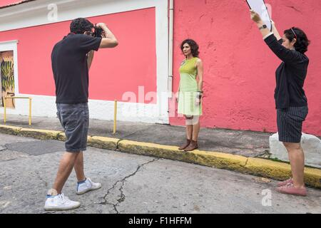 Behind the scenes of an urban fashion shoot with female model and male photographer - Stock Photo