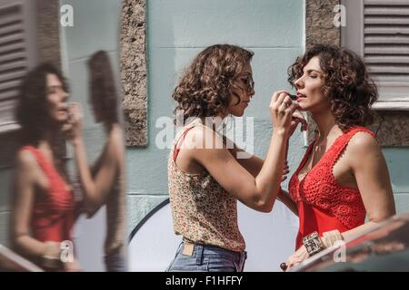 Behind the scenes of an urban fashion shoot with make up artist applying lipstick to model - Stock Photo