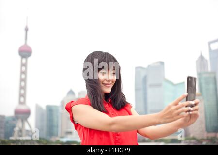 Young woman looking at smartphone, outdoors, Shanghai, China - Stock Photo