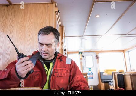 Engineer on boat speaking on walkie talkie to engineers on wind turbine at offshore windfarm - Stock Photo