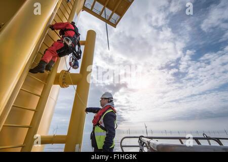 Engineer climbing wind turbine at offshore windfarm - Stock Photo