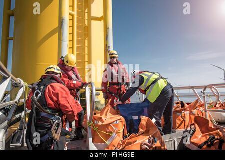 Engineers on boat preparing to climb wind turbine on offshore windfarm - Stock Photo