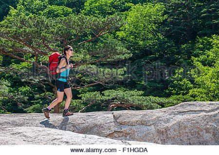 Woman hiking over a rocky ridge on the way to Mt. Ulsanbawi at Seoraksan national park, Gangwon, South Korea - Stock Photo