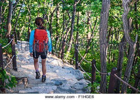 Woman hiking down a rocky trail on the way from Mt. Ulsanbawi at Seoraksan national park, Gangwon, South Korea - Stock Photo
