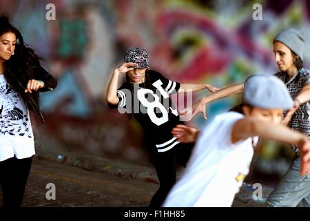 Young women breakdancing against street art - Stock Photo