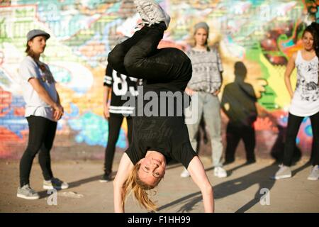 Young women in a breakdancing handstand freeze - Stock Photo