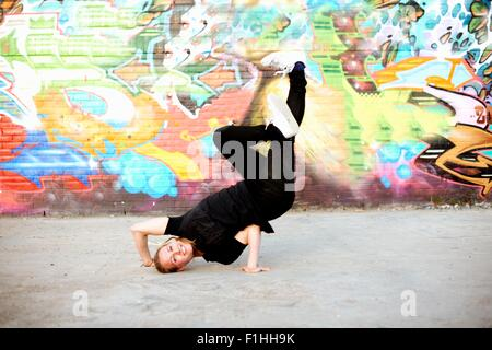 Young woman in upside down breakdancing freeze against graffiti - Stock Photo