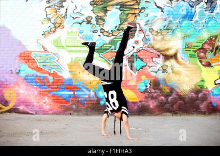 Young women in handstand breakdancing freeze against graffiti - Stock Photo