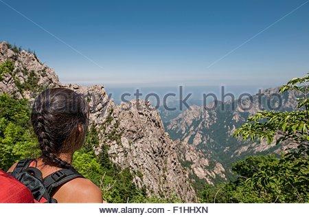Female hiker enjoying the view along a ridge,  Seoraksan National park, Gangwon, South Korea - Stock Photo