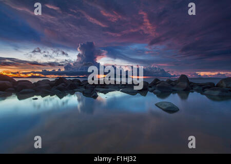 Cumulonimbus cloud reflection in Kura-Kura Beach, West Kalimantan, Indonesia. - Stock Photo