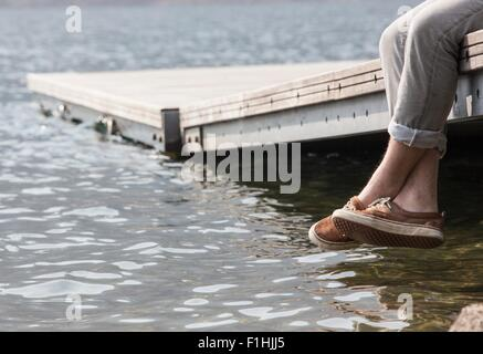 Legs of young man dangling from pier - Stock Photo