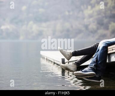 Legs of young couple dangling from pier at Lake Mergozzo, Verbania, Piemonte, Italy - Stock Photo