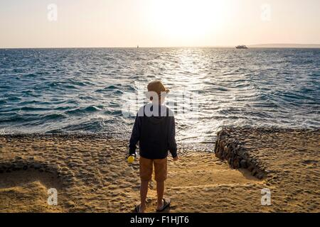 Young boy standing by sea, looking at view, rear view, Hurgada, Red Sea, Egypt - Stock Photo