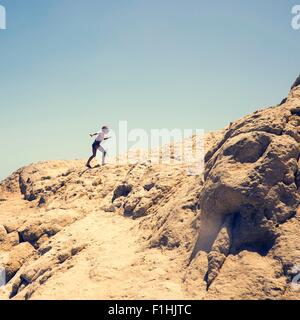 Young boy climbing sandy hill, Hurgada, Red Sea, Egypt - Stock Photo