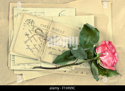 Old letters and dry rose flower. Vintage postcards and envelopes. Retro style toned picture - Stock Photo
