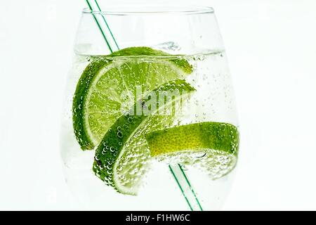 Slices of lime in a glass of fizzy drink with a straw on a white background - Stock Photo