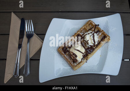 Delicious sweet waffle with cream and ice-cream in a waffle shop in Bruges, Belgium. A  perfect way to start the - Stock Photo