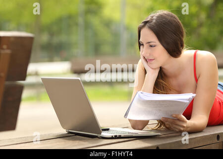 Concentrated student girl studying with a laptop lying in a bench in an university campus - Stock Photo