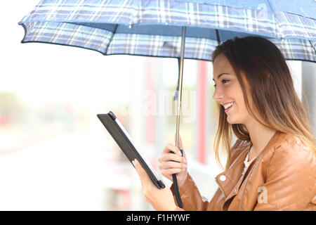 Profile of a woman reading ebook or tablet under an umbrella in a rainy day in a generic place - Stock Photo