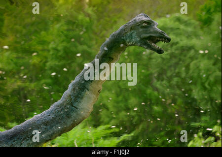 Reflection in pond of Nessie, the Loch Ness monster, outside the Loch Ness Exhibition Centre at Drumnadrochit, Scotland, - Stock Photo