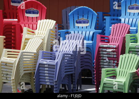 Colorful plastic chairs stacked up - Stock Photo