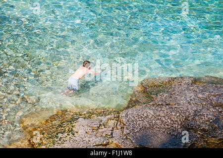 young boy swimming in the beautiful clear clean waters of Lake Huron at Bruce Peninsula National Park - Stock Photo