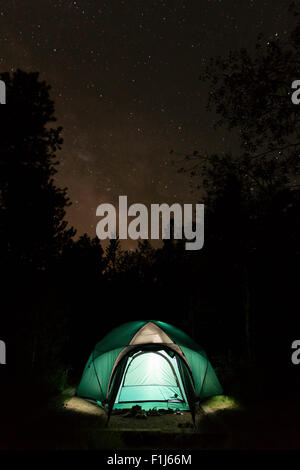 Tent camping under a clear, starry Colorado night sky.  The tent glows from within while the Milky Way Galaxy shines - Stock Photo