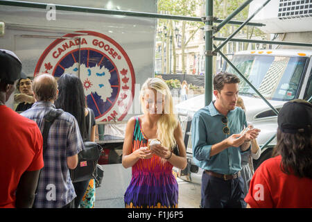 Ice cream lovers line up for a cool treat from the Coolhaus ice cream truck courtesy of the Canada Goose outdoor - Stock Photo