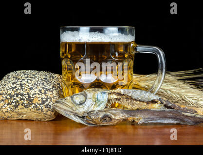 Pint of beer with bread, mackerel and wheat on black background. - Stock Photo