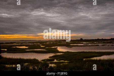 Sunsets' afterglow as ominous clouds roll in over Assateague Island - Stock Photo