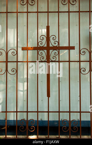 Cross added onto a window screen on 24th Street in The Mission in San Francisco, California. - Stock Photo