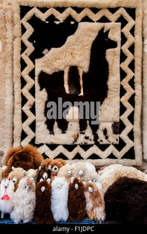 Traditional dolls llamas sitting on a pile of textiles - Stock Photo