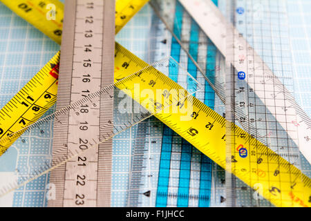 Rulers. Various types, transparetn, plastic, metal, laid out on pale blue measuring grid board - Stock Photo