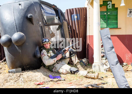 American army, black Hawk re-enactment. Weary looking soldier taking cover by downed helicopter - Stock Photo