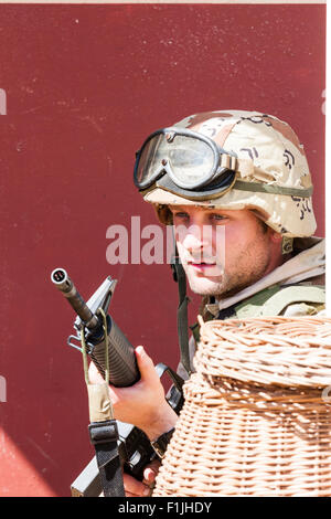 American army, black Hawk re-enactment, War and Peace show. Soldier taking cover behind basket, holding M16 at the - Stock Photo