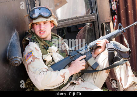 American army, black Hawk re-enactment. Weary looking soldier taking cover by downed helicopter, holding M16 rife - Stock Photo