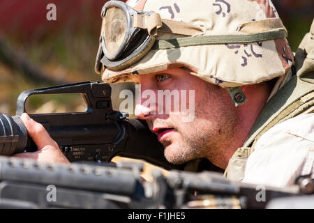 American army, black Hawk re-enactment, War and Peace show. Soldier laying down, aiming gun. side view. Desert camouflage - Stock Photo