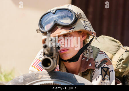 American army, black Hawk re-enactment, War and Peace show. Woman soldier laying down facing, aiming gun directly - Stock Photo