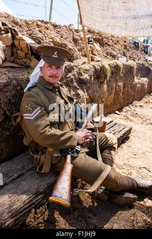 World war one re-enactment, British 1914 trench, with soldier, corporal  sitting with rifle on lap, head turned - Stock Photo