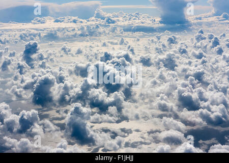 Cumulus clouds seen from above over the English Channel. Harsh directional sunlight on the clouds with clear blue - Stock Photo