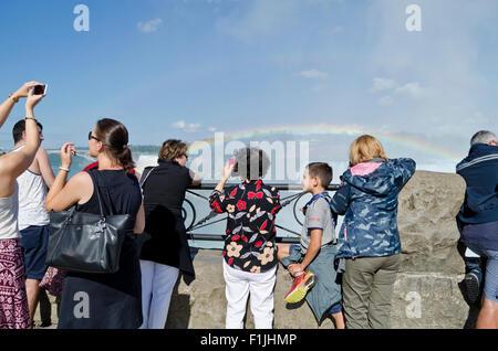 Tourists taking photos of Horseshoe Falls (Canadian) and rainbow in Niagara Falls Ontario Canada - Stock Photo