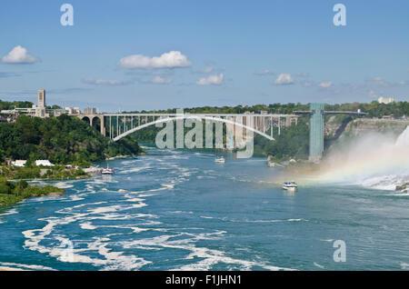 Rainbow Bridge between Canada and USA over the Niagara River in Niagara Falls. Ontario (left) and New York State - Stock Photo
