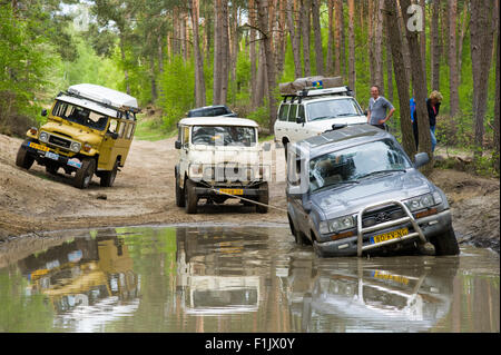 A Toyota Land Cruiser is stuck in a pond of water on a special off the road terrain for land cruisers and vehicles - Stock Photo