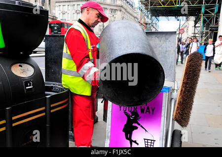 London, England, UK. Rubbish collector emptying a bin in Regent Street - Stock Photo