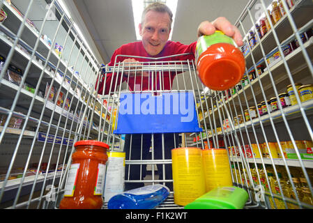 man shopping using trolley in supermarket - Stock Photo