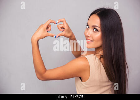 Portrait of a happy woman making heart gesture with fingers and looking at camera - Stock Photo