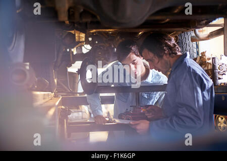 Mechanic and customer under car in auto repair shop - Stock Photo